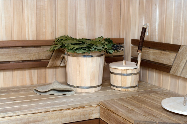 Picture: Inside the banya: fresh veniks, a felt hat, and a wooden bucket to add water on the wood stove and have a real steam bath!